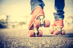 Cool man wearing roller skating shoes. Cool man with roller skating shoe using his mobile phone - Concepts of youthness,sport,lifestyle and 80s vintage style Stock Photography
