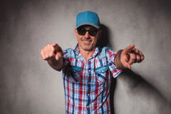 Cool mature casual man with trucker hat  pointing his fingers Royalty Free Stock Image