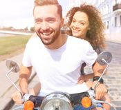 Happy cheerful couple riding vintage scooter outdoors. Cool men and beautiful girl riding on  scooter with  expression Stock Photo