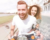Happy cheerful couple riding vintage scooter outdoors. Cool men and beautiful girl riding on  scooter with  expression Royalty Free Stock Image