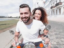 Happy cheerful couple riding vintage scooter outdoors. Stock Photo