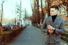 Cool men in fashion suit smoking a cigarette outside in the stre Stock Photo