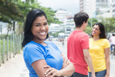 Cool mexican woman in a blue shirt with friends. Cool mexican women in a blue shirt with friends outdoor in the city Stock Photo