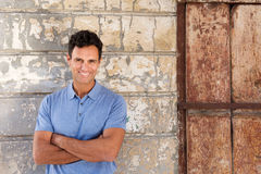 Cool middle age man smiling with arms crossed against wall Royalty Free Stock Photos