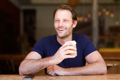 Cool middle age man smiling with coffee cup at cafe. Portrait of cool middle age man smiling with coffee cup at cafe Royalty Free Stock Photography