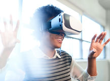 Cool millennial black woman exploring virtual reality glasses in an open-concept space. Smiling young African American woman with VR glasses reaching out and Royalty Free Stock Images