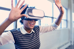 Cool millennial black woman exploring virtual reality glasses in an open-concept space. Smiling young African American woman with VR glasses reaching out and Stock Photo