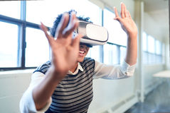 Cool millennial black woman exploring virtual reality glasses in an open-concept space. Smiling young African American woman with VR glasses reaching out and Stock Photos
