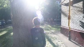 Cool mixed boy walking outside of his house after school stock video footage