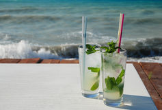 Cool Mojitos my the sea. Cool mint mojitos cocktails sitting by the blue sea stock photography
