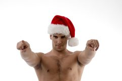 Cool muscular man wearing christmas hat. And pointing towards with white background Royalty Free Stock Photo