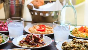 Ouzo in short glasses with ice. Appetizers of seafood in plates. Blur backdrop, close up, details Stock Image
