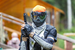 Cool paintball fighter in special armor holding paint handgun. Royalty Free Stock Photos