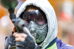 Cool paintball player with marker aiming in camera. Closeup. Stock Photo