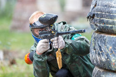 Cool paintball player shooting from marker outdoors Stock Image