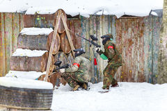 Cool paintball in winter. Two shooters behind fortifications. Stock Photo