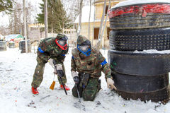 Cool paintball in winter. Two shooters behind fortifications. Royalty Free Stock Images