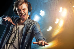 Cool party DJ man with headphones. Young modern style handsome man in headphones playing music. Dynamic background Stock Photo