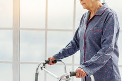 Cool pensioner holding foldable walker while going in clinic Royalty Free Stock Image