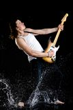 Cool performer. Portrait of young performer playing electrical guitar in water splashes Royalty Free Stock Photo