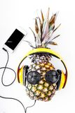 Cool pineapple in sunglasses is music lover. White background top view Royalty Free Stock Photo