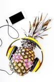 Cool pineapple in sunglasses is music lover. White background top view Royalty Free Stock Photography