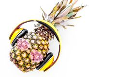 Cool pineapple in sunglasses is music lover. White background top view copyspace Stock Photo
