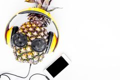 Cool pineapple in sunglasses is music lover. White background top view copyspace Royalty Free Stock Photo