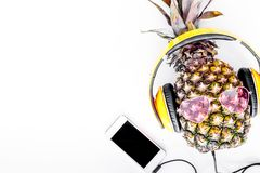 Cool pineapple in sunglasses is music lover. White background top view copyspace Royalty Free Stock Images