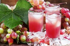 Cool pink grape juice with ice, selective focus. Food still life stock photography