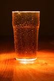 Cool pint of Lager. Cold pint of lager on a polished wooden bar Royalty Free Stock Photography
