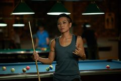 Cool player. Cool Asian female billiard player showing rock gesture Stock Photo