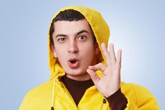 Cool pleasant looking male with dark hair, wears yellow anorak and hood, shows okay sign, agrees with something, shows his approva. L, has confident and happy Stock Photos