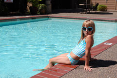Cool at the pool. Young girl poses like a movie star by the pool Royalty Free Stock Image
