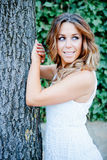 Cool pretty woman leaning on a tree trunk Stock Images