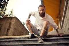 Cool przyglądającego faceta obsiadanie w ulicie na schodkach Fotografia Royalty Free