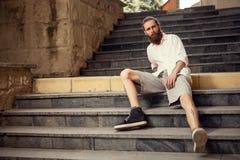 Cool przyglądającego modnisia obsiadanie w ulicie na schodkach Obraz Royalty Free