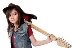 Cool punk rocker girl with guitar on her back, on white background. Cool Asian punk rocker grl in jeans jacket and fedora hat doing a pose with electric guitar stock photography