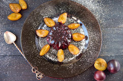 Cool purple jelly with fresh fruits and powder decorated with plums and silver spoon on dark plate on black wooden background