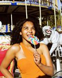 Cool real modern teenage girl with candy near carousels at amuse. Ment park walking, having fun Stock Photo