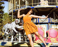 Cool real teenage girl with candy near carousels at amusement pa Royalty Free Stock Photo