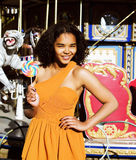 Cool real teenage girl with candy near carousels at amusement pa Royalty Free Stock Photography