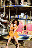 Cool real teenage girl with candy near carousels at amusement pa Royalty Free Stock Images