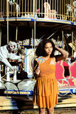 Cool real teenage girl with candy near carousels at amusement pa Royalty Free Stock Image