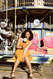 Cool real teenage girl with candy near carousels at amusement pa Stock Images