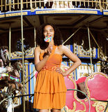 Cool real teenage girl with candy near carousels at amusement pa Stock Photography