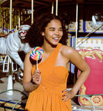 Cool real teenage girl with candy near carousels at amusement park walking, having fun Stock Photos