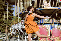 Cool real teenage girl with candy near carousels at amusement park walking, having fun Royalty Free Stock Photo
