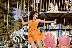 Cool real teenage girl with candy near carousels at amusement park walking, having fun Royalty Free Stock Images