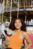 Cool real teenage girl with candy near carousels at amusement park walking, having fun Royalty Free Stock Image